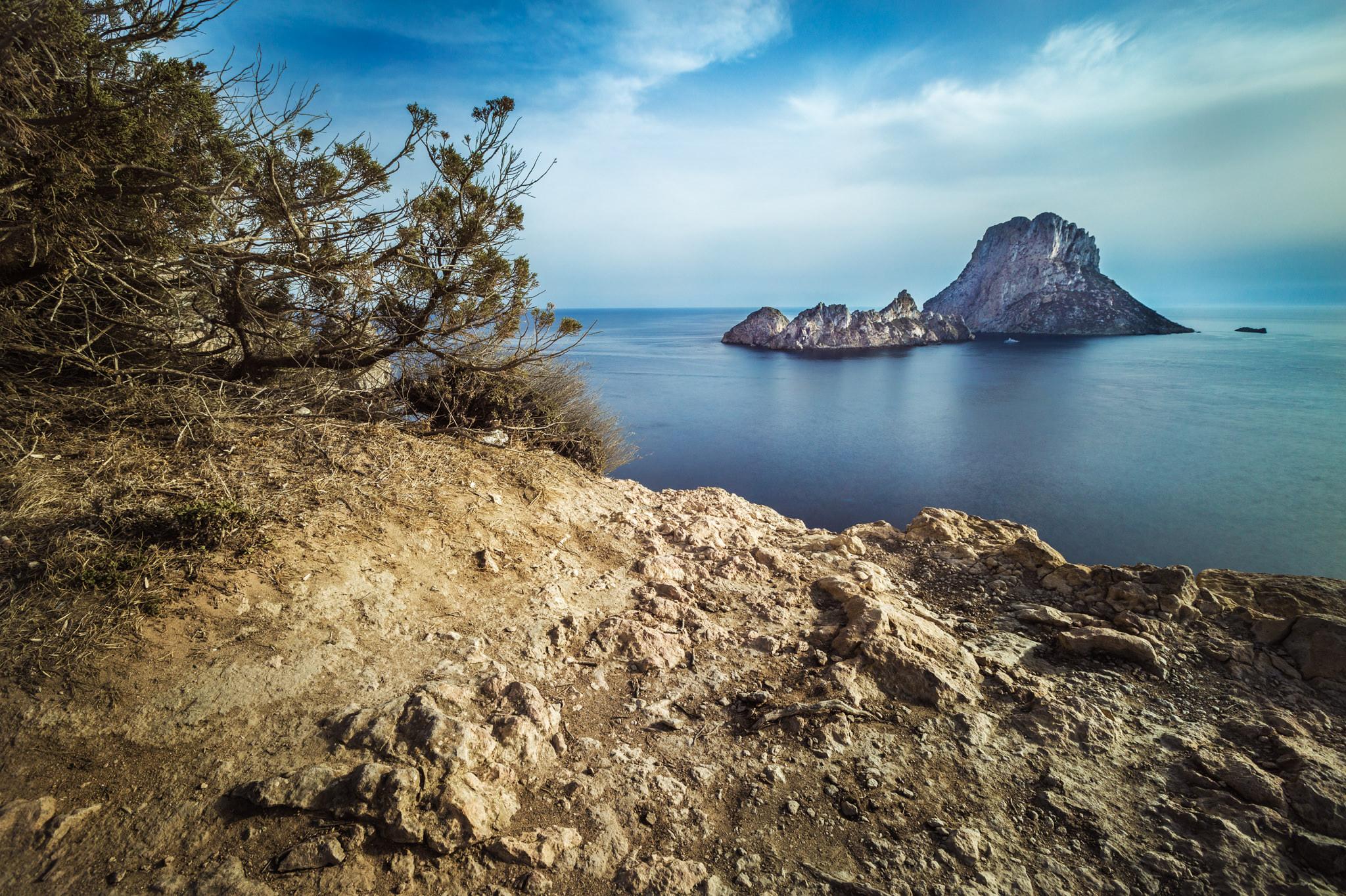 Fotografía de paisaje de larga exposición en la que aparece la isla de Es Vedra, en Ibiza, enmarcada por un paraje natural de piedra y bosque